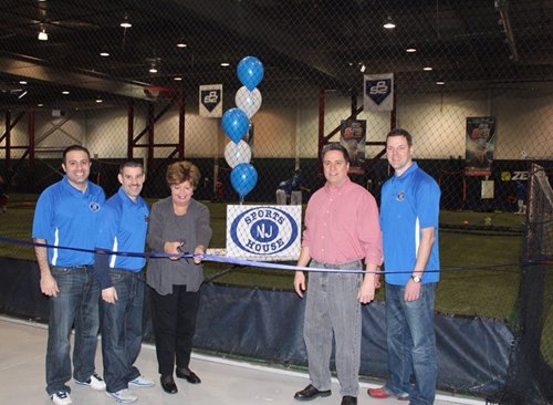 Oakland's Mayor Linda Schwager cuts the Grand Opening Day ribbon while Recreation Chairman Mike Guadagnino and the NJ Sports House owners, (L-R in blue) Mike Carti, Frank Morano and Chris Hughes look on.