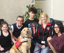 """Barnstable Academy's middle school students along with Dr. Rebecca Eliason, Director of Social Services, enjoyed the afternoon learning about the process, meeting Cassie, and experimenting with behaviors.    Cassie demonstrated how she responds to people who are anxious, frightened, lonely, sad, or just need a friendly visit.  """"We are very appreciative that Mrs. Alpert brought Cassie in to teach us about dog therapy and the training process,"""" said Eliason.  """"They helped us experience the benefits of this type of intervention,"""" Eliason added."""